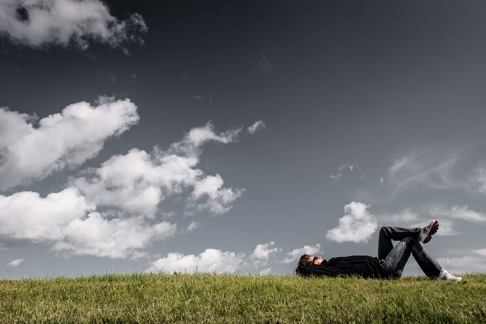 Mann som ligg i graset og kikar opp på himmelen