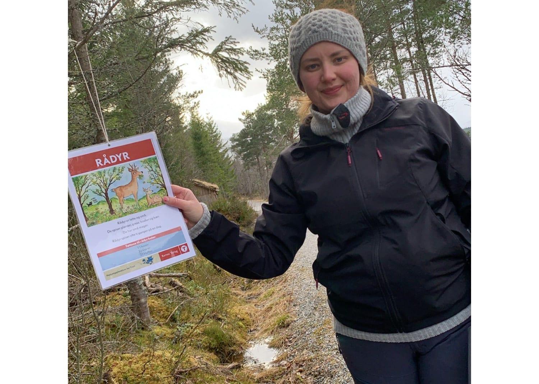 Ann-Iren Aas viser fram ein av postane som Barnas turlag Vestnes har hengt opp i Kråkvika friluftsområde.