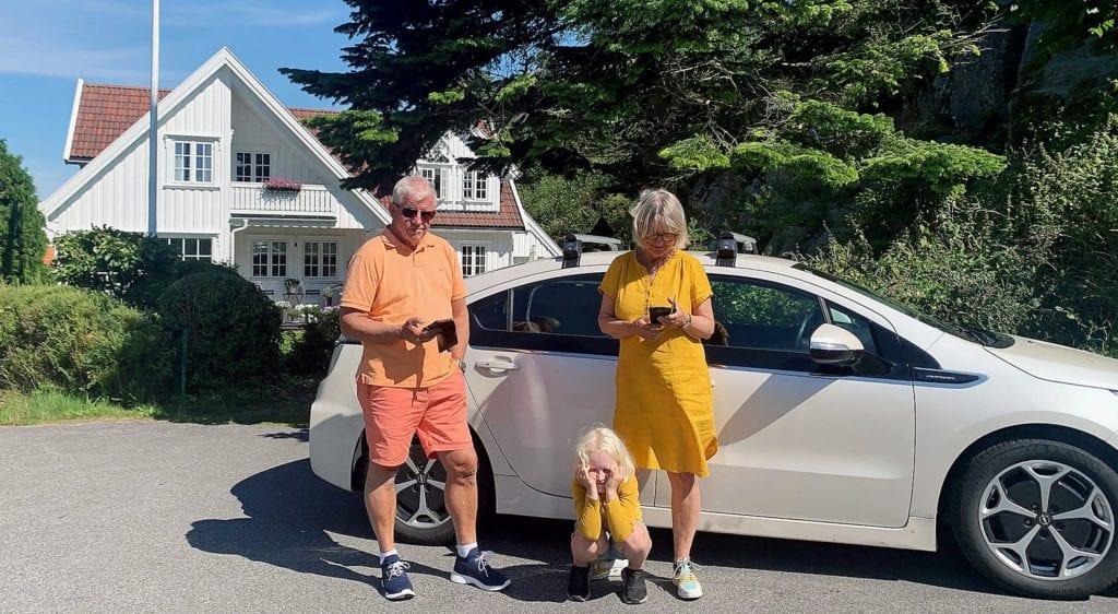 Familie utanfor kvit bil ein solskinnsdag om sommaren.